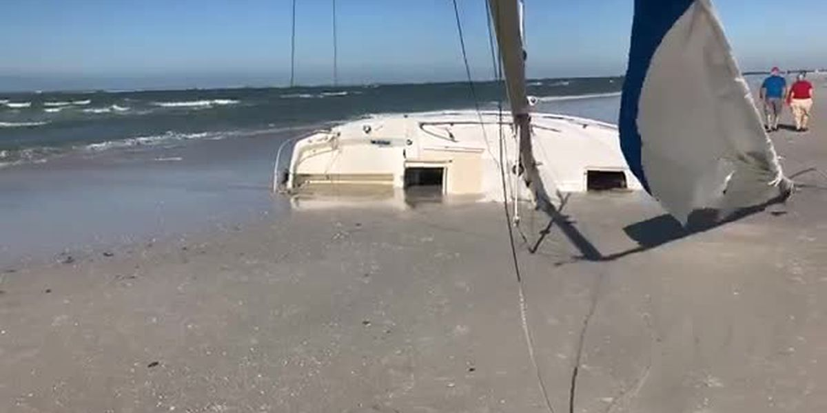 Sailboat grounded in sand at Siesta Key