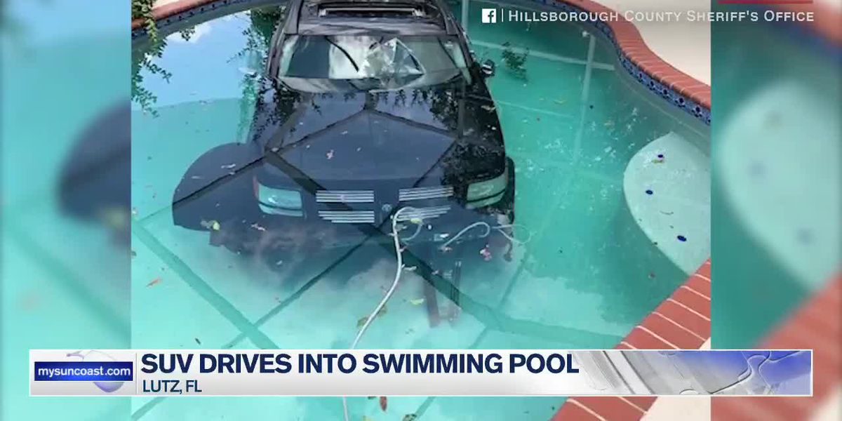 SUV drives into swimming pool